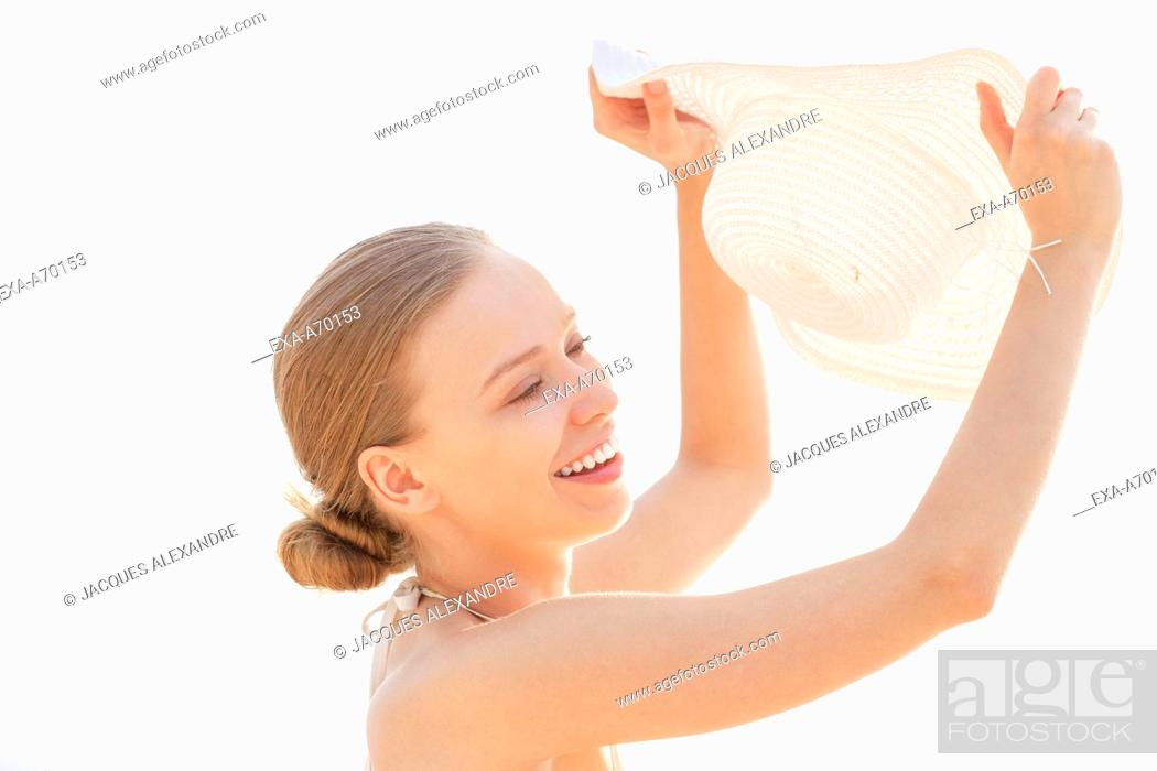 Stock Photo: woman with white sun hat protecting her face against sun.