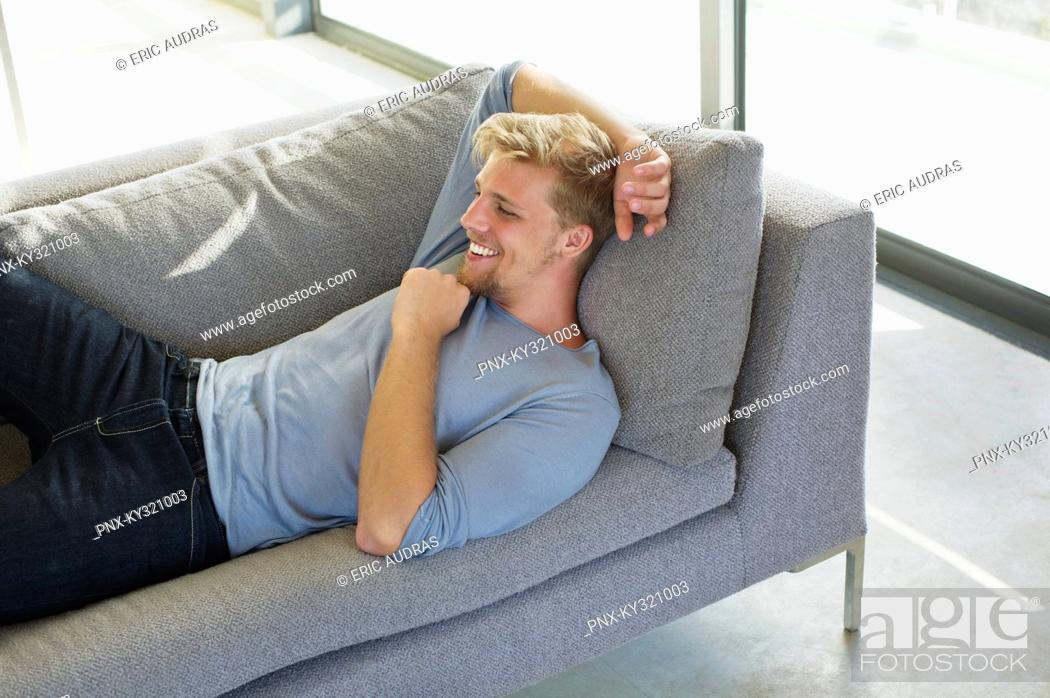 Stock Photo: High angle view of a young man lying on a couch at home and smiling.
