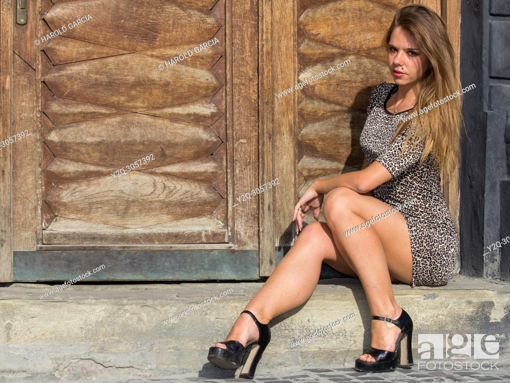 Imagen: Sexy and elegant Ukrainian woman wearing a leopard skin print dress posing seated and reclining to one side in front of a large wooden door for a photographic.