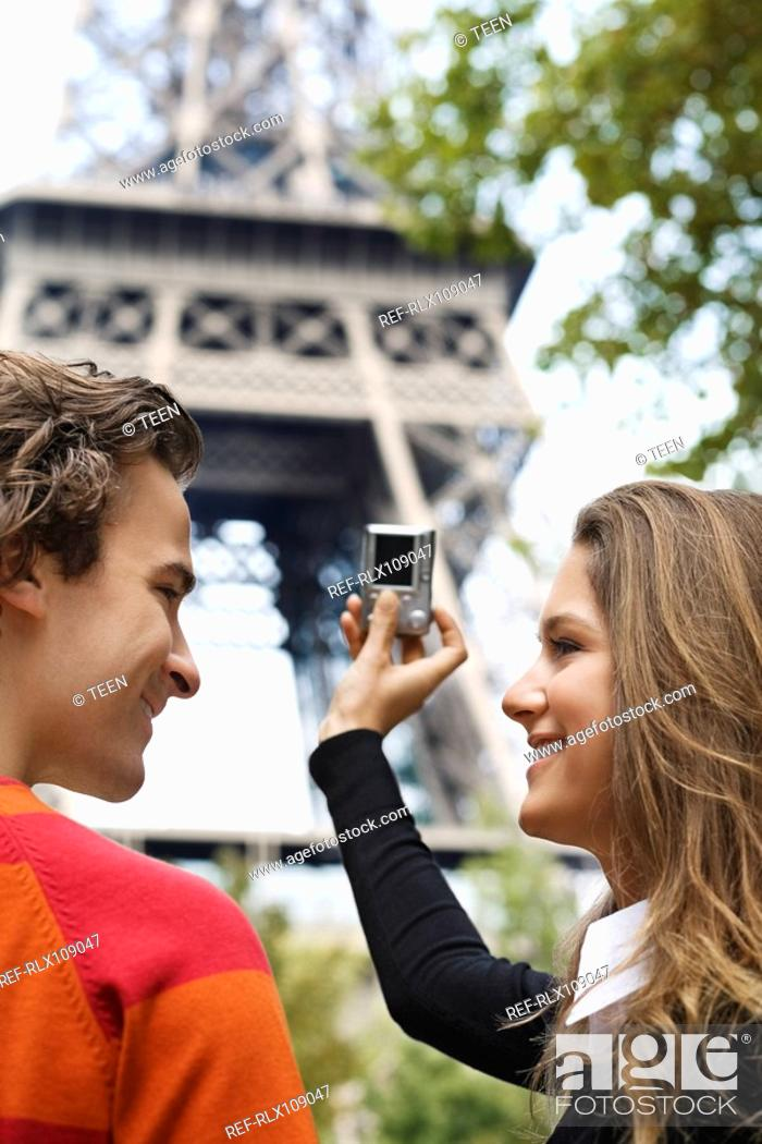 Stock Photo: Young couple taking picture of Eiffel tower, Paris, France.