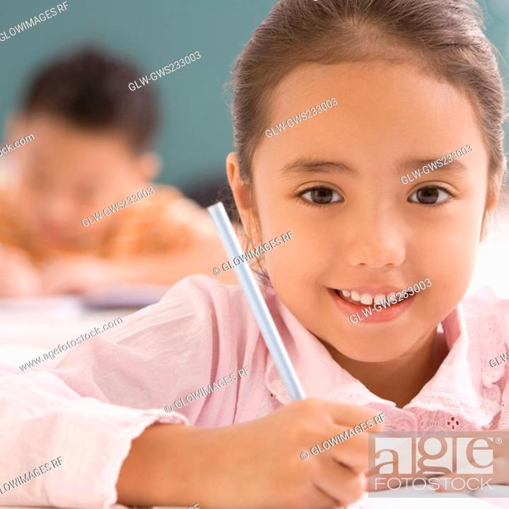 Stock Photo: Portrait of a schoolgirl writing on a notebook with a pencil and smiling.