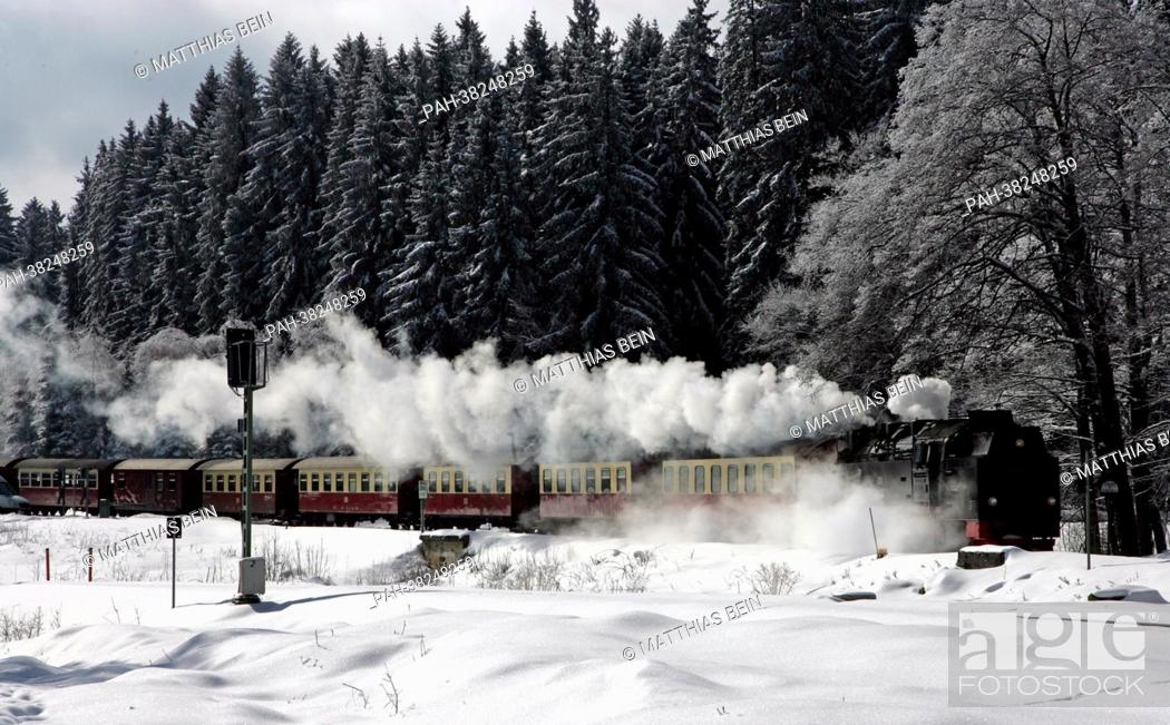 Stock Photo: A steam train engine of the Harz narrow-gauge railway services travels through a wintery öandscape in the Harz region near Wernigerode, Germany, 13 March 2013.