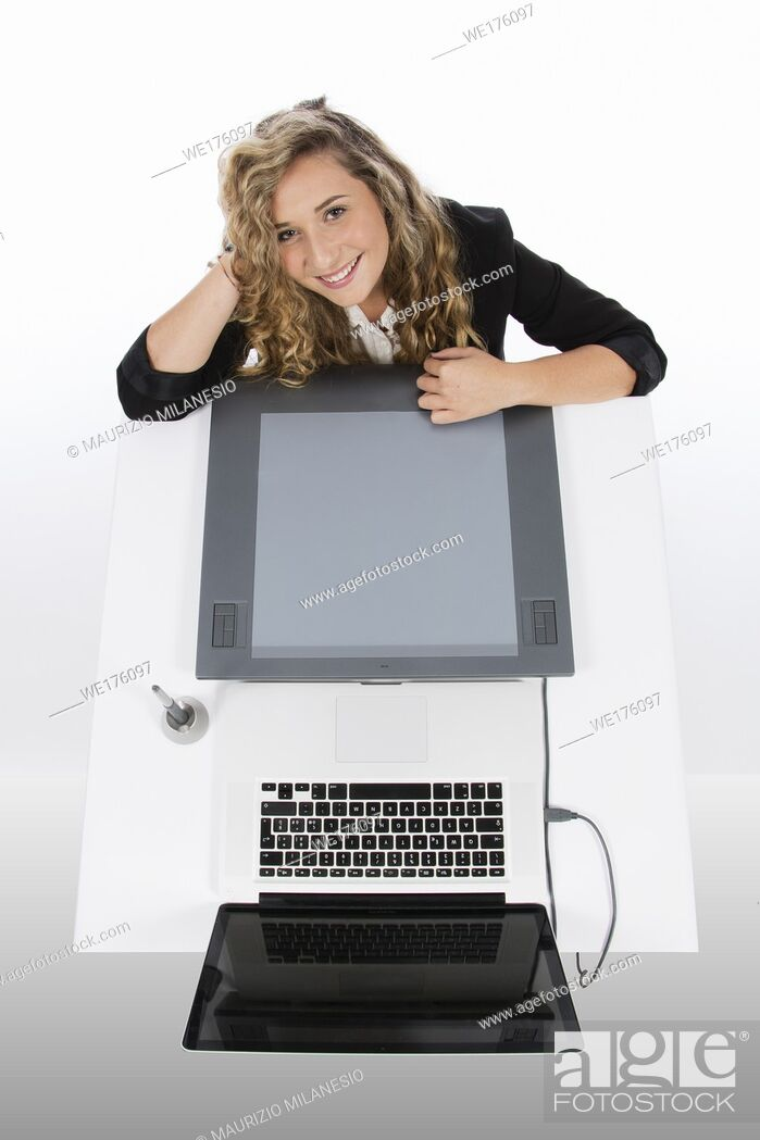 Stock Photo: Graphic designer seen from above with a tablet and a laptop, she is smiling and with her arms resting on the desk and her head.