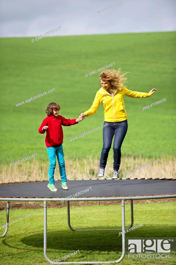 Stock Photo: Woman with her son jumping on a trampoline in a field.