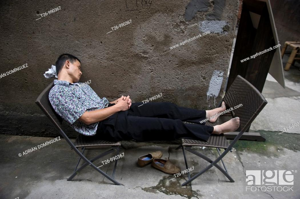 Stock Photo: A man sleeps between two chairs.