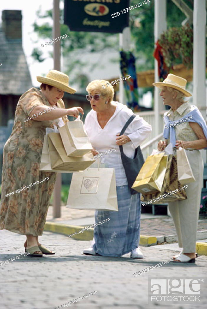 Stock Photo: Three senior women walking with shopping bags.