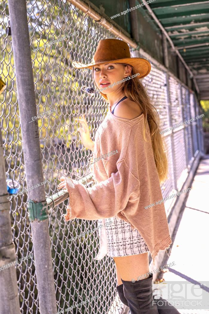 Photo de stock: A 15 year old girl standing next to a wire fence wearing a large hat looking at the camera.