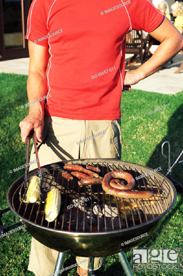 Stock Photo: Man cooking food on a barbecue.