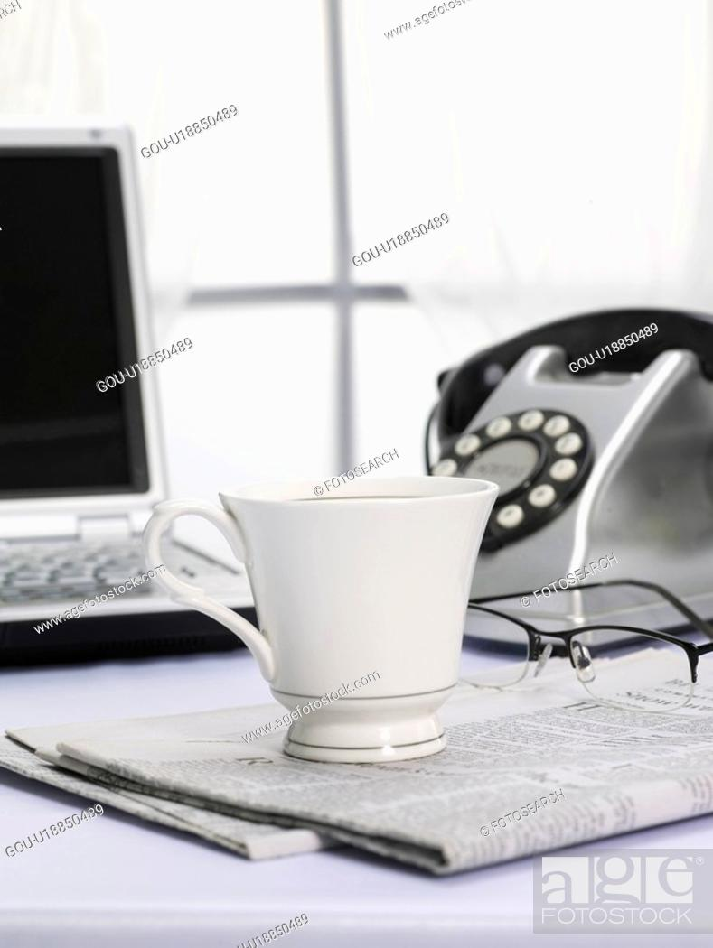 Stock Photo: newspaper, notebook computer, telephone, eyeglasses, laptop, window, coffee cup.