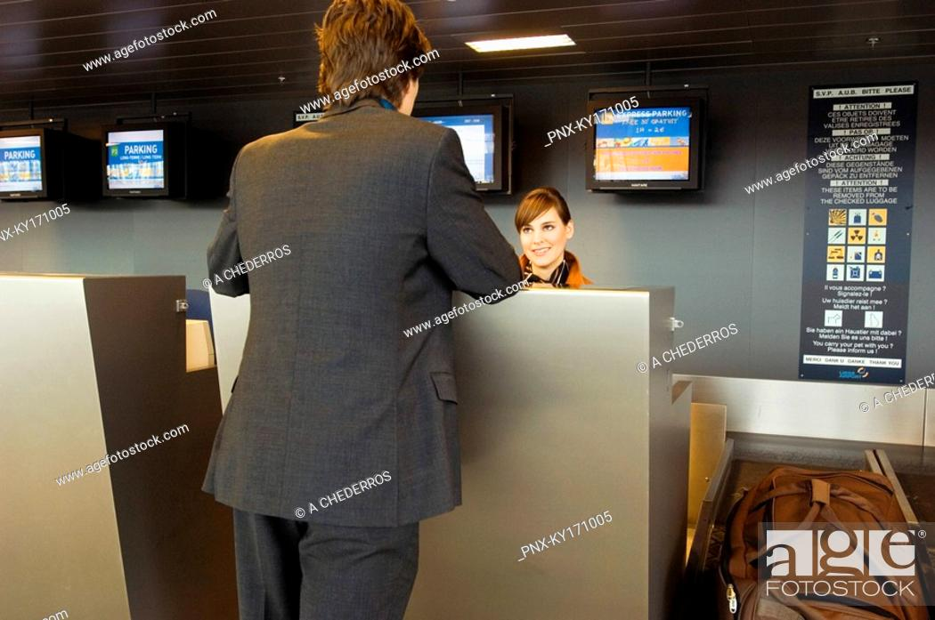 Stock Photo: Rear view of a businessman standing at an airport check-in counter.