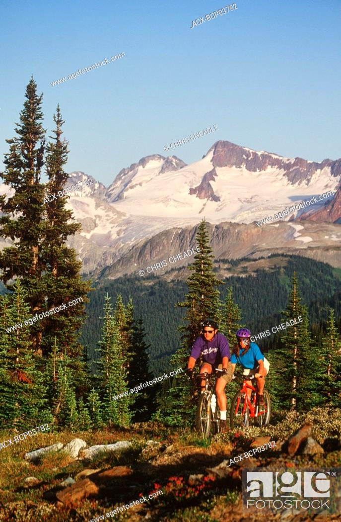 Stock Photo: young couple ride bikes in alpine area, Whistler, British Columbia, Canada.