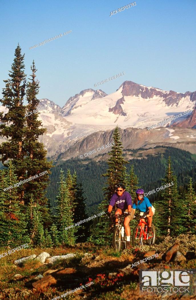 Stock Photo: young couple ride bikes in alpine area, Whistler, British Columbia, Canada.
