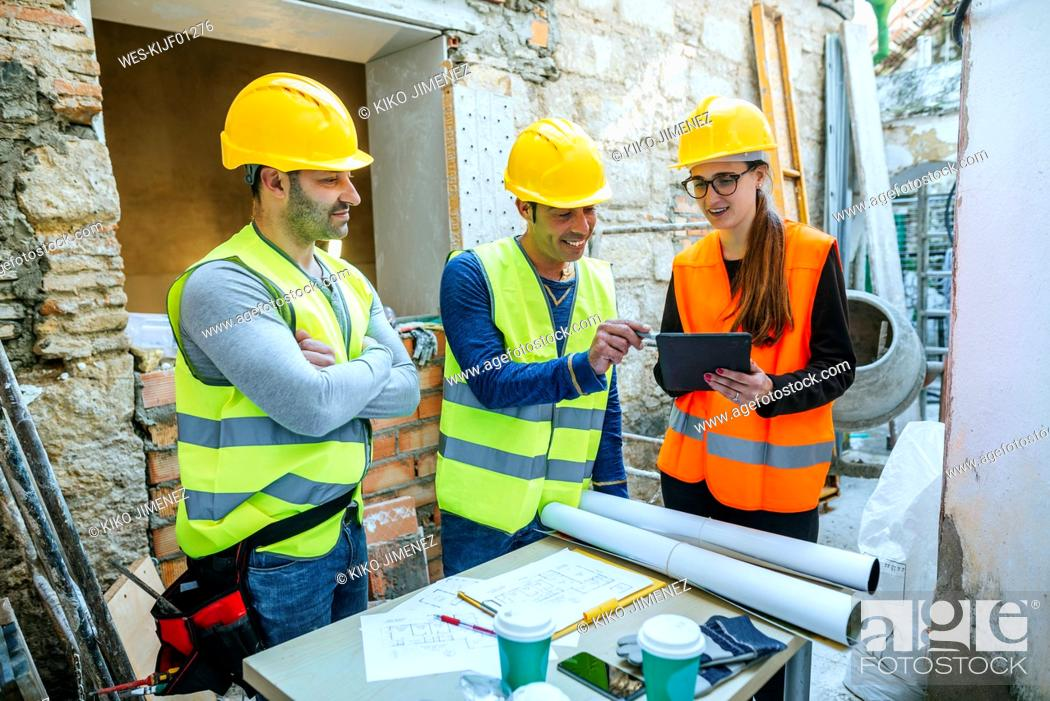 Stock Photo: Woman and two construction workers with tablet on construction site.