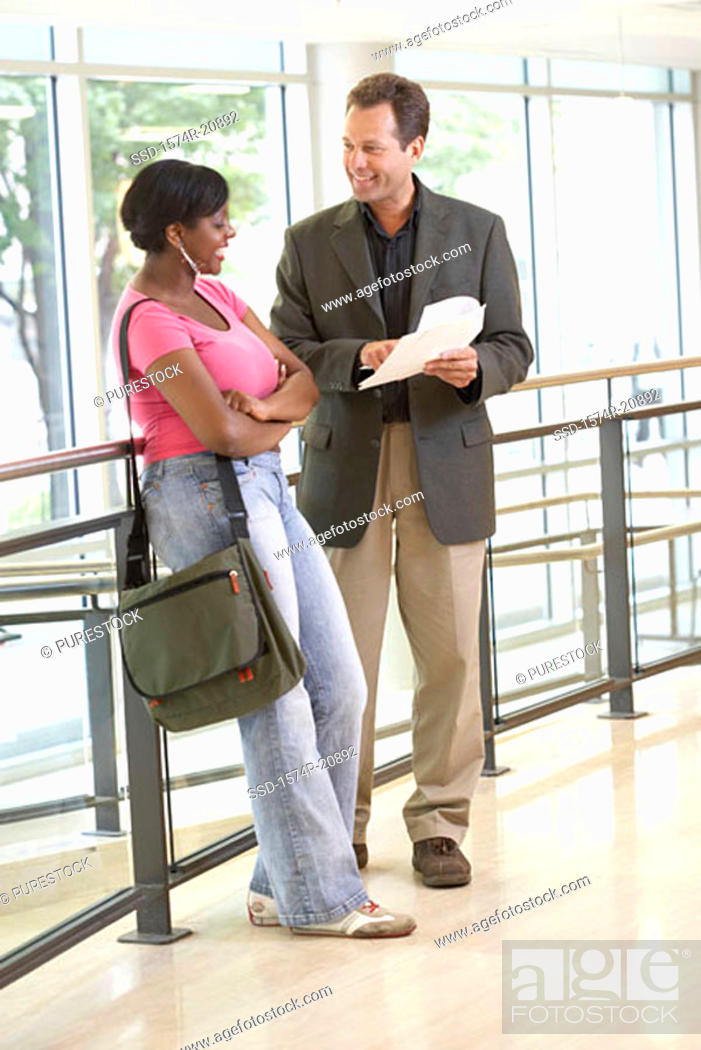 Stock Photo: Side profile of a college student standing with her professor in a corridor.