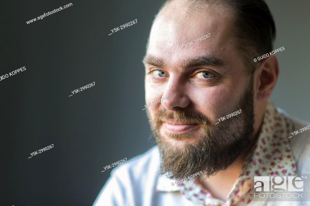 Stock Photo: Tilburg, Netherlands. Studio portrait of a adult, caucasian male telling personal an intimate stories, with a blurry, gray background behind him.