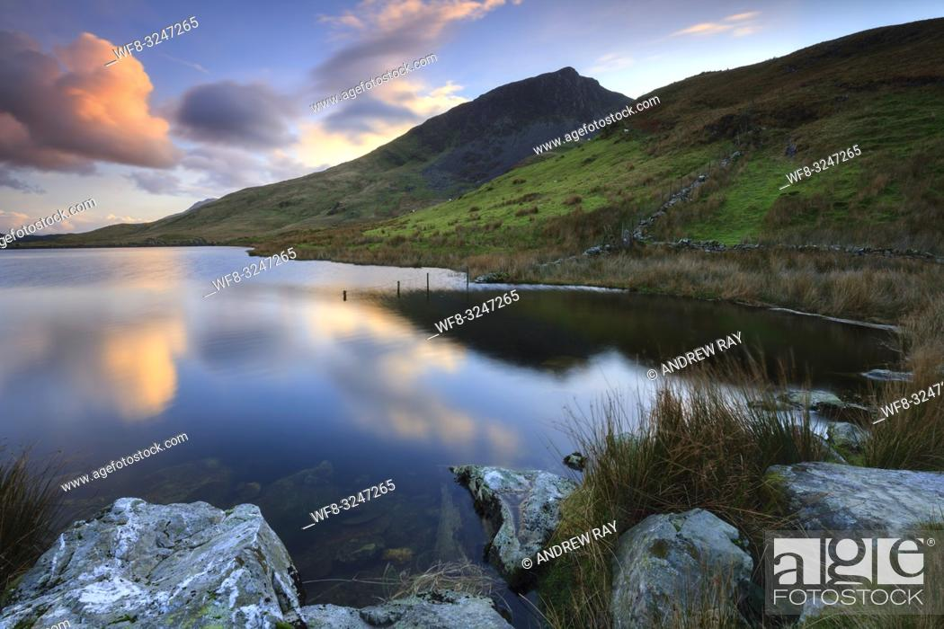 Imagen: Sunset captured from the northern shore of Llyn Dywarchen in the Snowdonia National Park in North Wales, with the prominent peak of Y Garn in the distance.