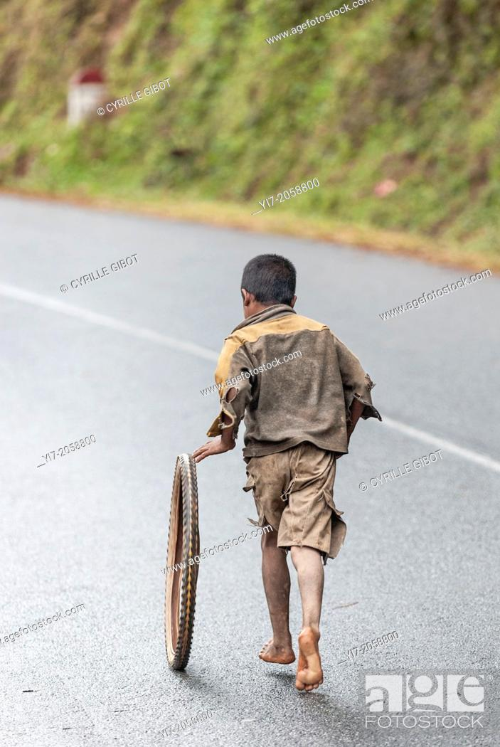 Stock Photo: Boy playing with a tire, Ranomafana, Madagascar.