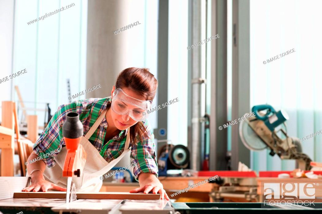 Stock Photo: Carpenter using saw in workshop.