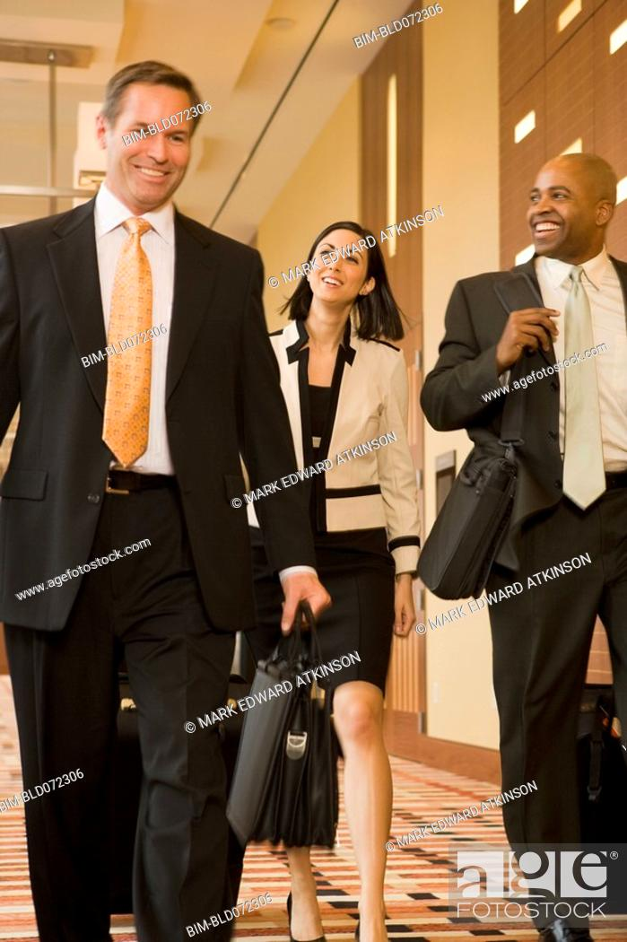 Stock Photo: Multi-ethnic business people walking with suitcases down corridor.