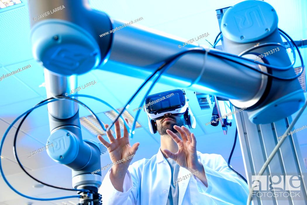 Stock Photo: Robotic arm with artificial vision, Researcher with virtual reality glasses, VR, Humanoid robot for automotive assembly tasks in collaboration with people.