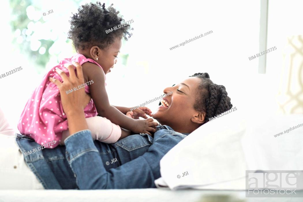 Stock Photo: Black woman playing with baby daughter on bed.