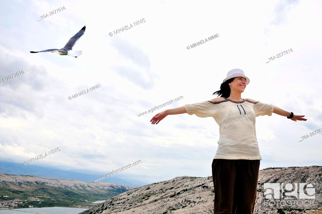 Stock Photo: Portrait of smiling mid adult woman with outstretched arms.