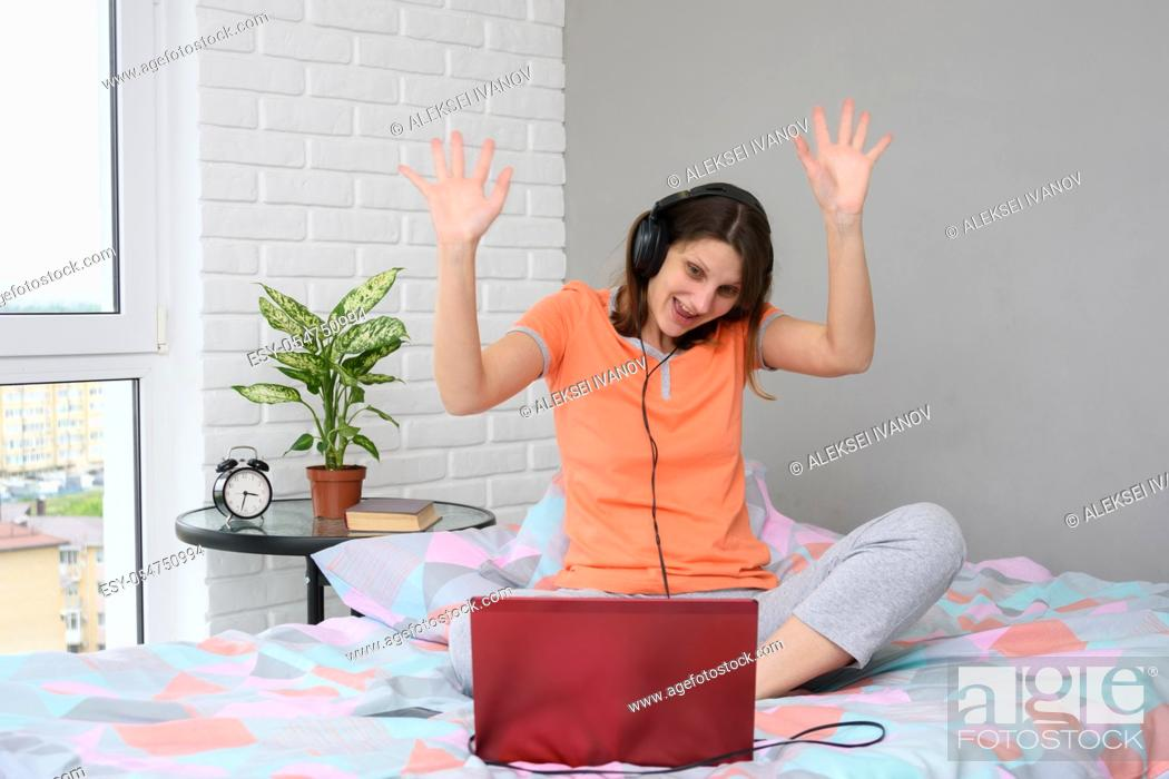 Stock Photo: The girl is funny and welcoming waving her hands while looking at the laptop screen.