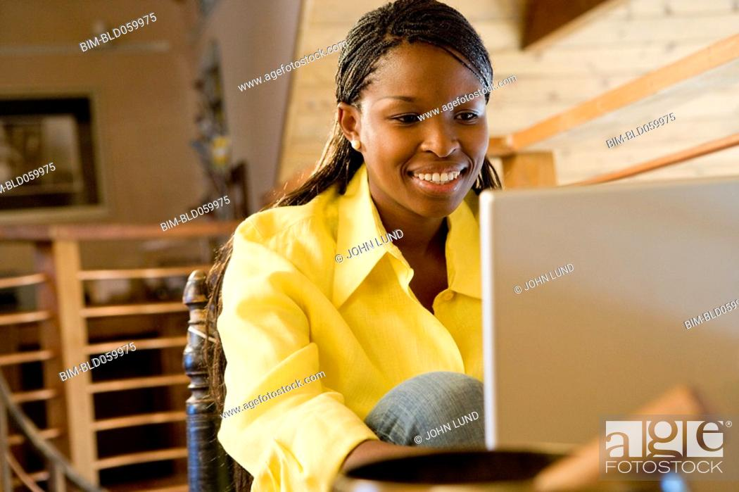 Stock Photo: African woman looking at laptop.
