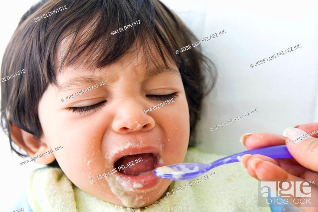 Stock Photo: Crying Hispanic baby being fed.