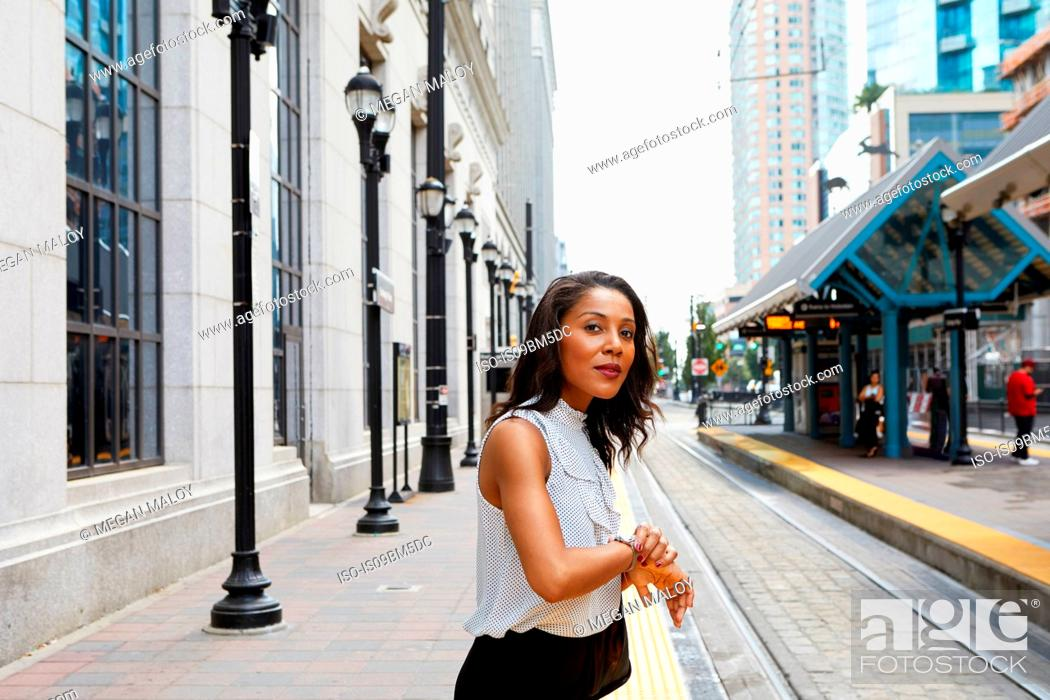 Stock Photo: Businesswoman checking time by light rail line.