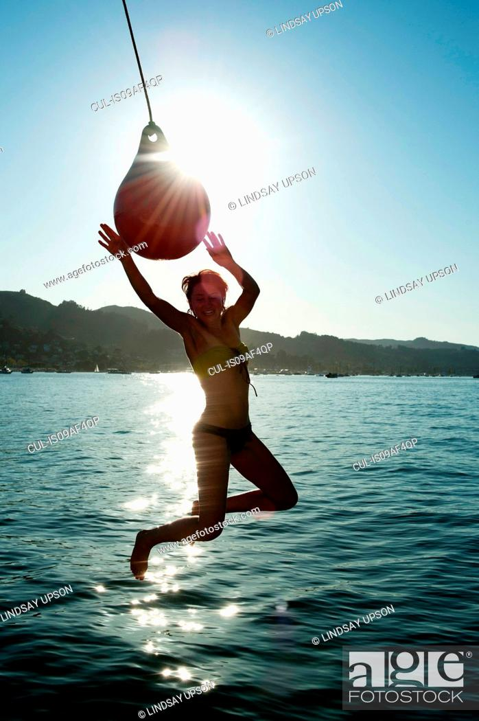 Stock Photo: Young woman swinging from boat fender, Sausalito, California, USA.