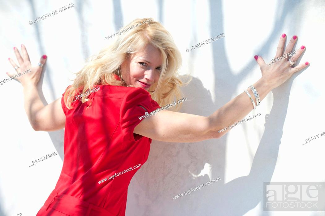 Stock Photo: Portrait of a smiling 44 year old blond woman, outdoors looking over her shoulder with arms spread on to a white wall.