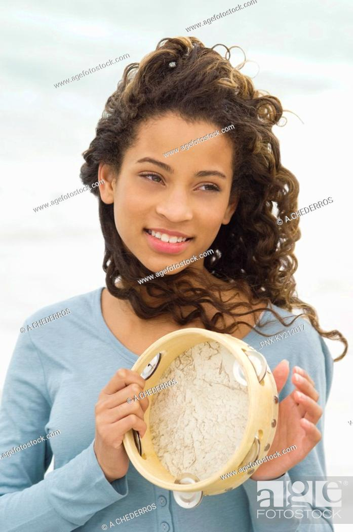 Stock Photo: Close-up of a girl playing a tambourine.