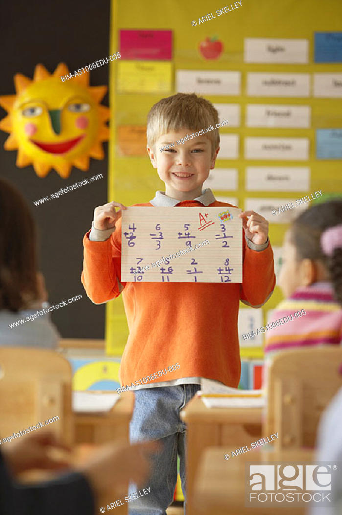 Stock Photo: Boy holding paper up in front of class.
