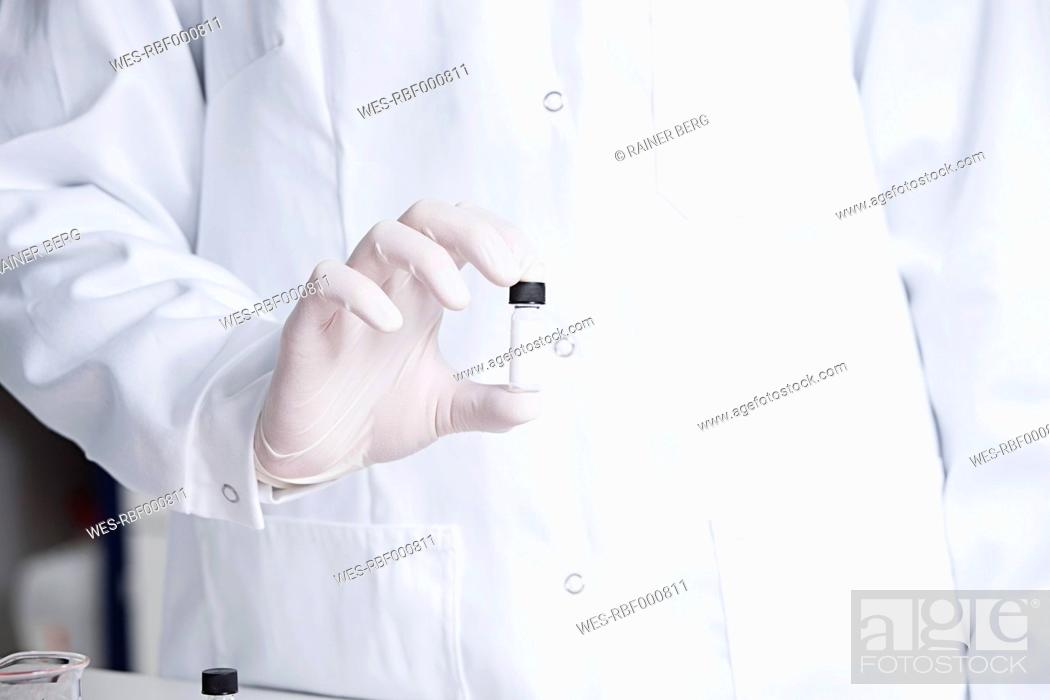 Stock Photo: Germany, Bavaria, Munich, Scientist holding phial for medical research in laboratory.