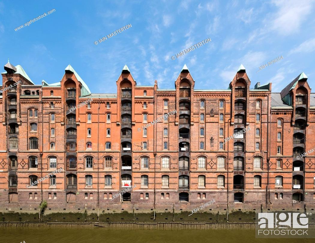 Stock Photo: View of historic red brick warehouses at Speicherstadt beside canals in Hamburg Germany.
