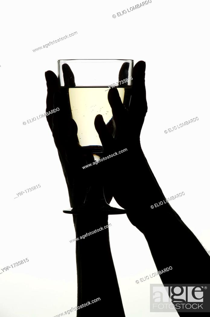 Stock Photo: Woman's hands holding a glass of white wine.