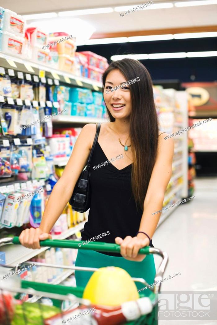 Stock Photo: A young woman shopping in supermarket.
