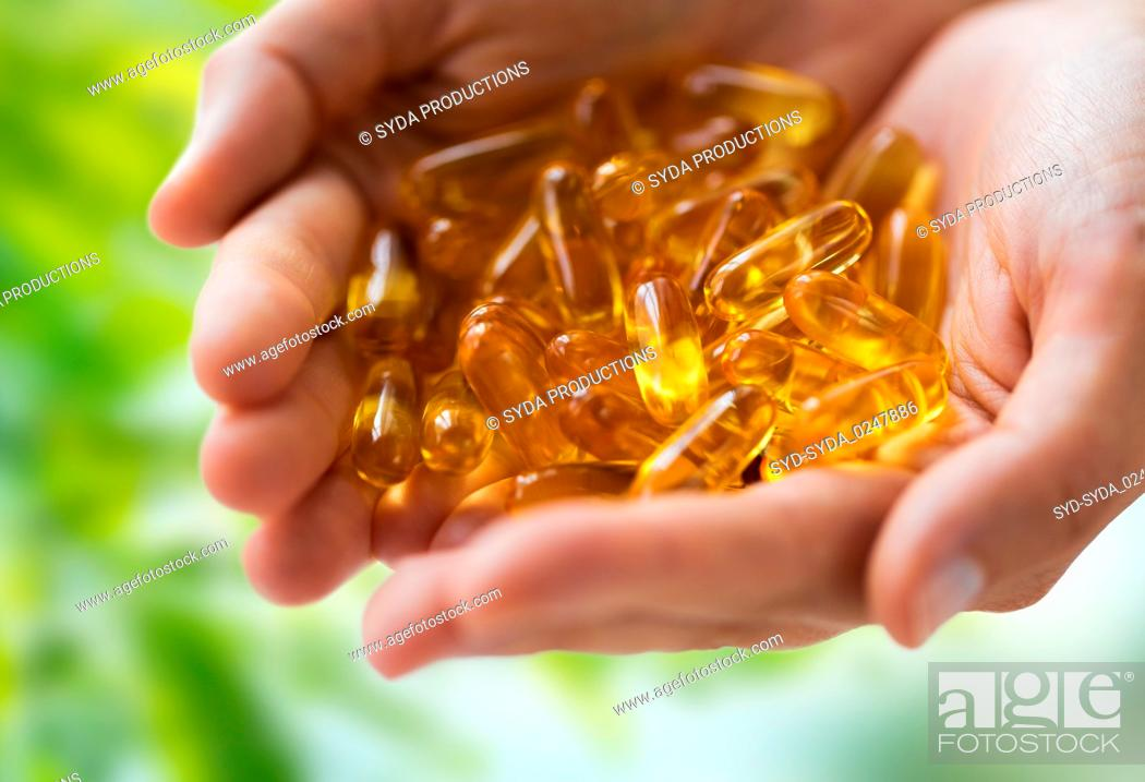 Imagen: hands holding cod liver oil capsules.
