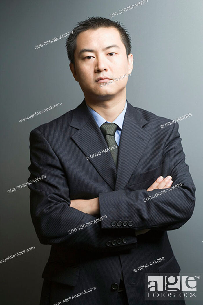 Stock Photo: Businessman standing with arms crossed.