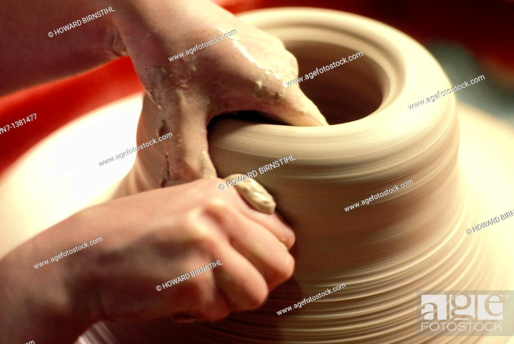 Stock Photo: close up of a potter's hands as he carefully shapes his clay on the turning wheel.