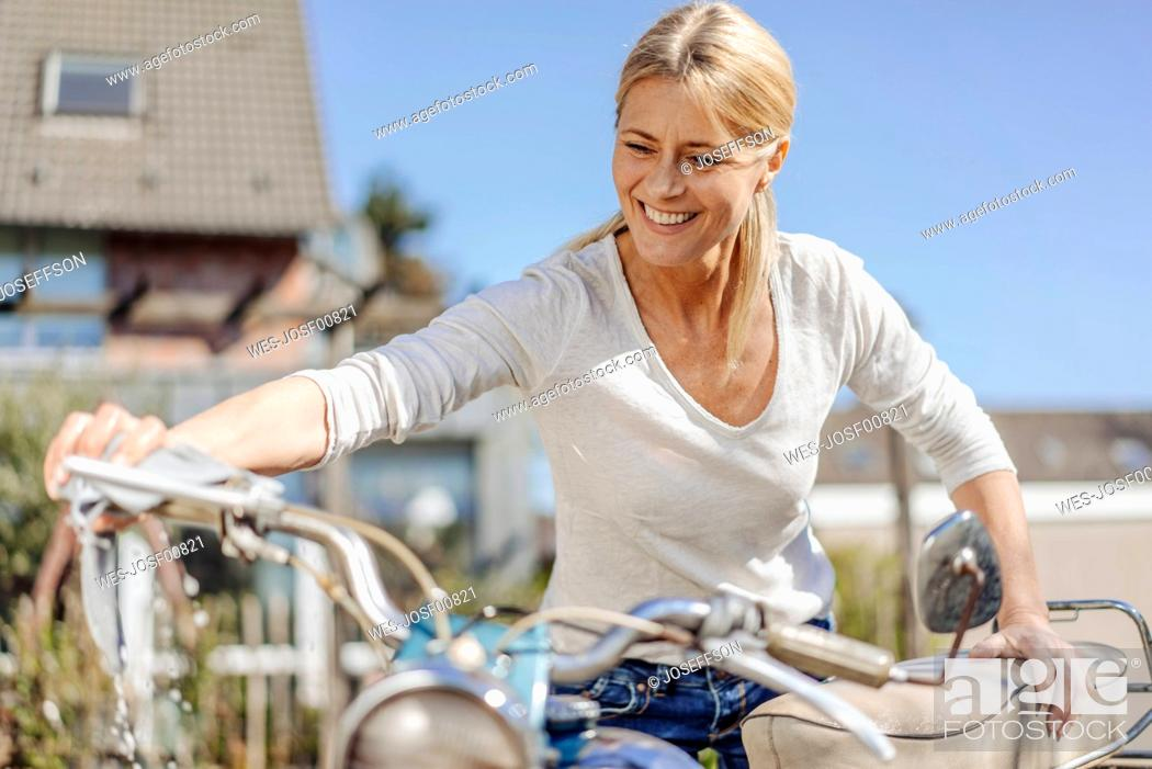 Stock Photo: Smiling woman cleaning vintage motorcycle.