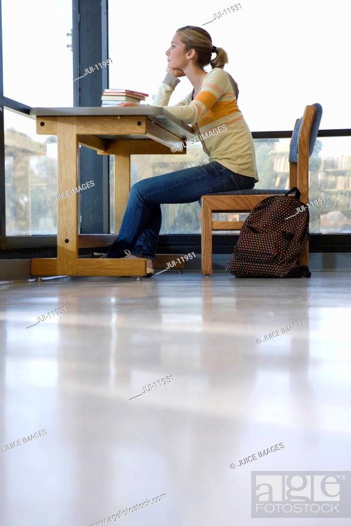 Stock Photo: Young female student at desk, chin in hand, low angle view.