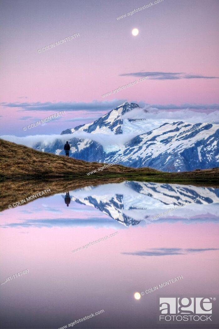 Stock Photo: Mt Aspiring, tramper enjoys moonrise at dusk, Cascade Saddle tarn, Mount Aspiring National Park, Otago, New Zealand.