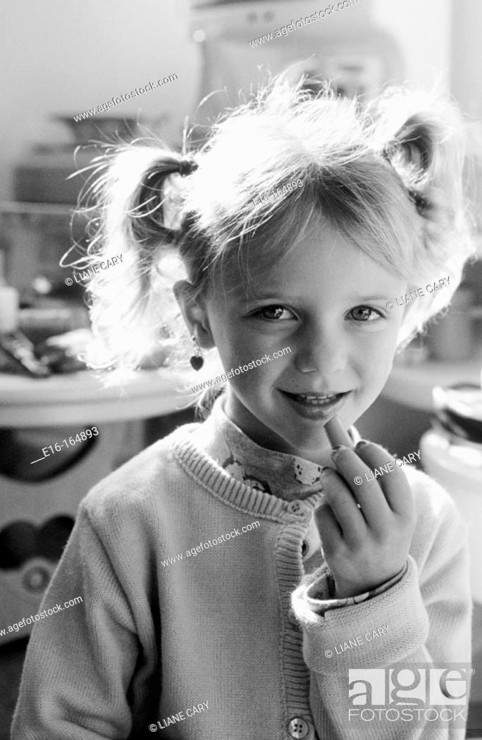 Stock Photo: Girl putting on pretend makeup.