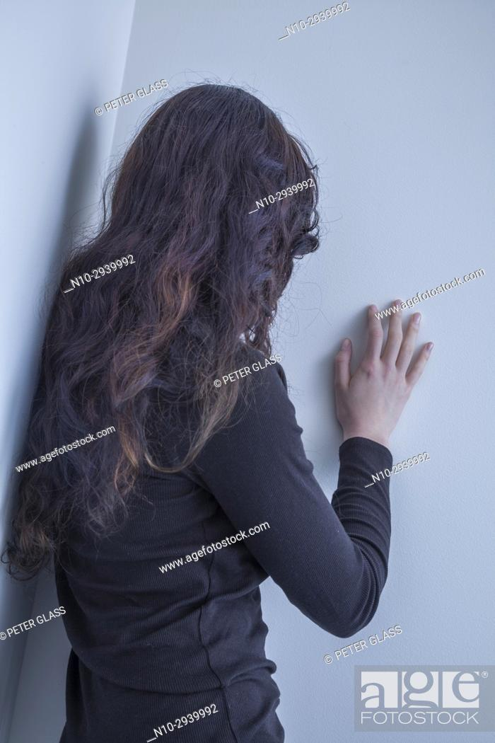 Stock Photo: Teenage girl, back to camera, hand on a wall.