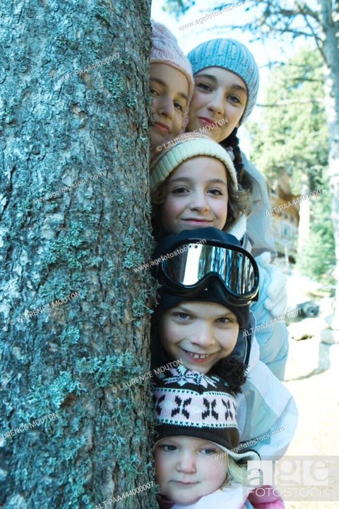 Stock Photo: Kids and teens peeking from behind tree in ski clothes, portrait.