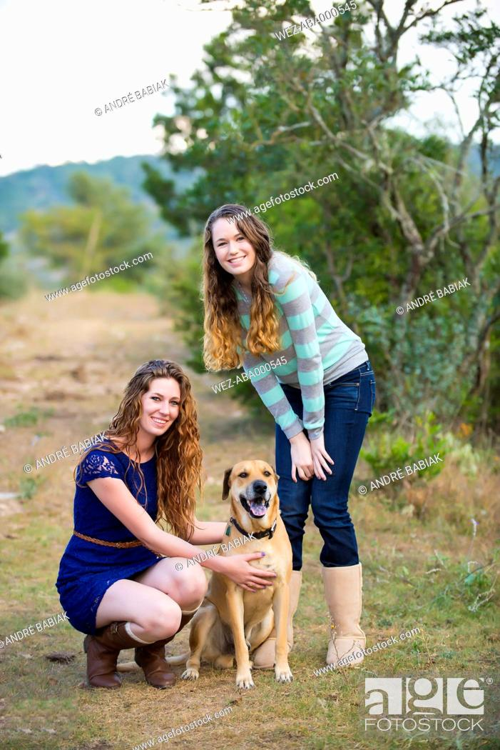 Stock Photo: USA, Texas, Sisters with Blackmouth Cur, smiling, portrait.