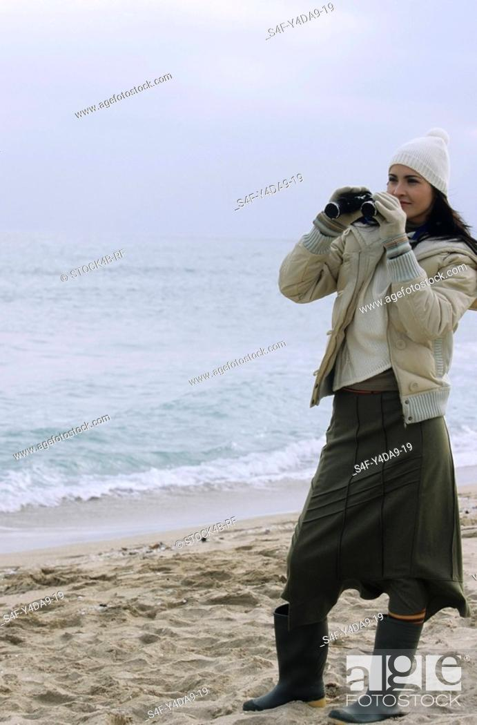 Stock Photo: Young brownhaired Woman with woolen Hat and Rubber Boots looking through Binoculars - View - Leisure Time - Coldness - Beach.