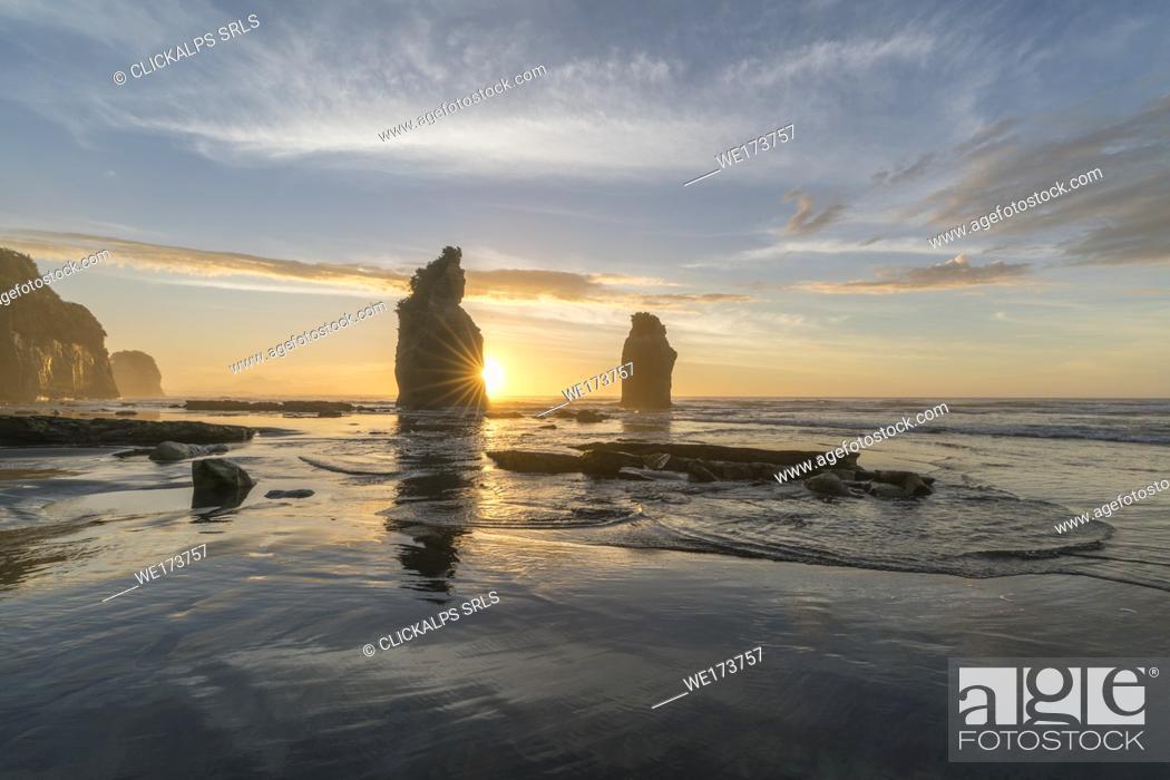 Stock Photo: The sun in setting down behind the Three Sisters. Tongaporutu, New Plymouth district. Taranaki region, North Island, New Zealand.